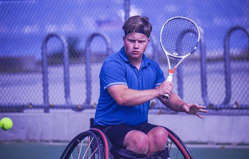 Thomas Venos prepares to hit a tennis ball. A young caucasian male sits in a tennis chair, holding a racket in his right hand. He's wearing a blue shirt and black shorts, a tennis ball heads towards him.